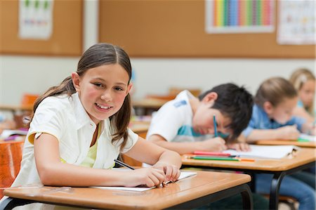 elementary school - Side view of smiling schoolgirl with her exercise book Stock Photo - Premium Royalty-Free, Code: 6109-06007460