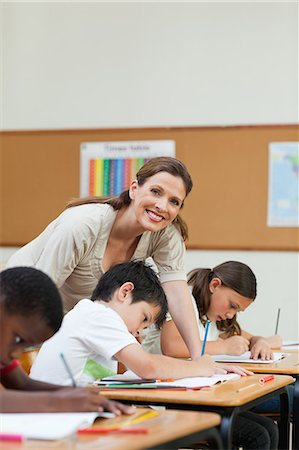 Side view of helpful elementary teacher next to a student Stock Photo - Premium Royalty-Free, Code: 6109-06007487