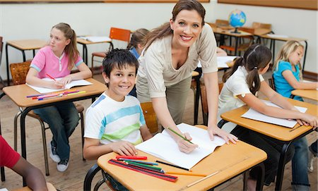 Smiling elementary teacher correcting students work Stock Photo - Premium Royalty-Free, Code: 6109-06007488