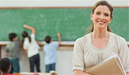 Smiling elementary teacher with students on blackboard behind her Stock Photo - Premium Royalty-Free, Code: 6109-06007577