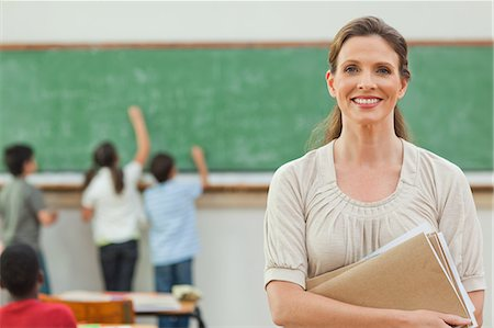 Smiling elementary teacher with students working on blackboard behind her Stock Photo - Premium Royalty-Free, Code: 6109-06007576