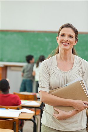 Smiling elementary teacher standing in classroom with books in her arms Stock Photo - Premium Royalty-Free, Code: 6109-06007579