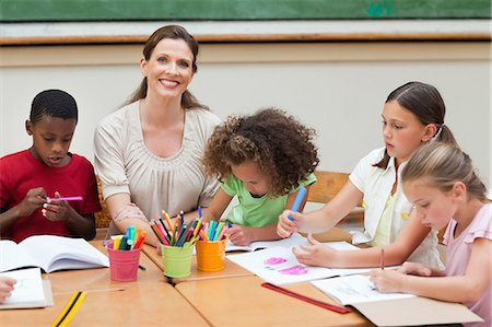 Smiling elementary teacher paining together her students Stock Photo - Premium Royalty-Free, Code: 6109-06007583
