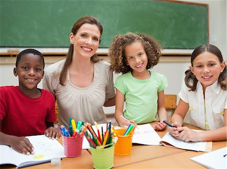 draw black women - Smiling elementary teacher sitting together with her students Stock Photo - Premium Royalty-Free, Code: 6109-06007587