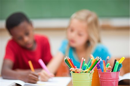 Pencil holders next to painting elementary students Stock Photo - Premium Royalty-Free, Code: 6109-06007591