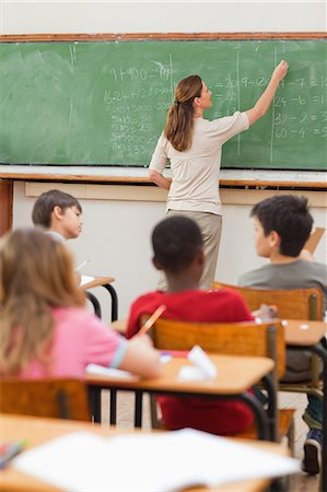 school desk - Elementary teacher writing math problems on blackboard Stock Photo - Premium Royalty-Free, Code: 6109-06007529