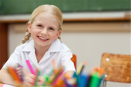 Smiling elementary student sitting at desk with pen Stock Photo - Premium Royalty-Free, Code: 6109-06007601