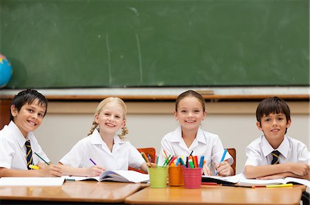 pretty pictures to draw - Smiling little schoolchildren sitting at desk together Stock Photo - Premium Royalty-Free, Code: 6109-06007617