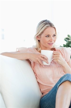 Beautiful blonde woman sitting on the sofa Stock Photo - Premium Royalty-Free, Code: 6109-06194243
