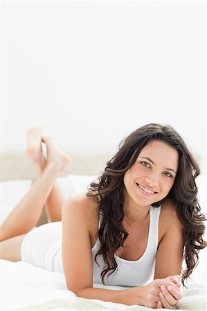 Close-up of a pretty brunette lying on her bed Stock Photo - Premium Royalty-Free, Code: 6109-06194367