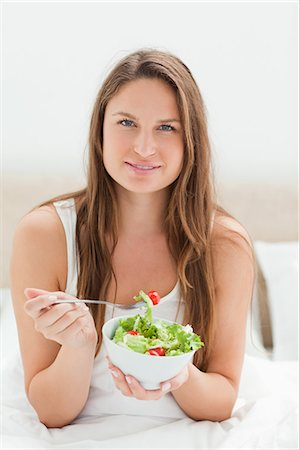 snack - Young woman eating a salad Stock Photo - Premium Royalty-Free, Code: 6109-06194418