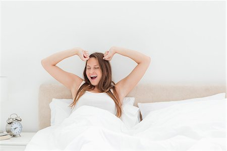 Young woman yawning and stretching her arms Stock Photo - Premium Royalty-Free, Code: 6109-06194428