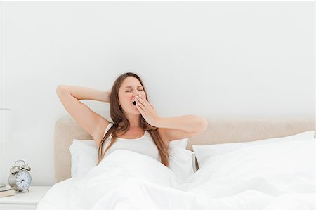 Cute woman yawning in her bed Stock Photo - Premium Royalty-Free, Code: 6109-06194429