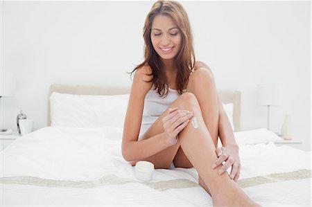 Smiling woman applying moisturizer Stock Photo - Premium Royalty-Free, Code: 6109-06194521