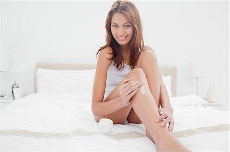Portrait of a smiling woman applying moisturizer Stock Photo - Premium Royalty-Free, Code: 6109-06194522