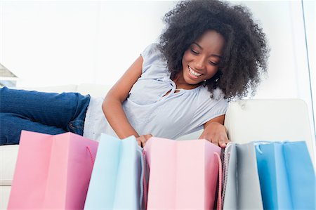 Happy fuzzy hair woman looking into her shopping bags Stock Photo - Premium Royalty-Free, Code: 6109-06194703