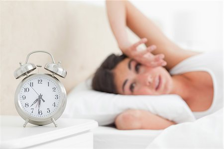 Cute brunette waking up by her alarm Stock Photo - Premium Royalty-Free, Code: 6109-06194892