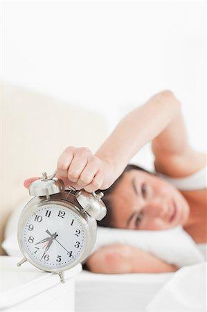 Brunette hating her alarm Stock Photo - Premium Royalty-Free, Code: 6109-06194894