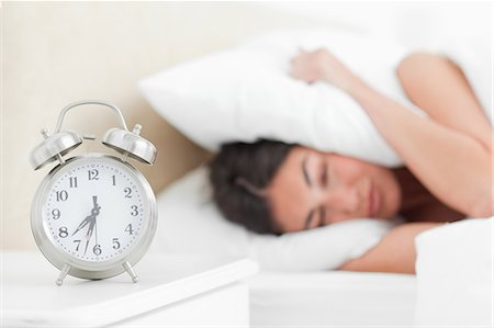 Rude awakening for a student with her alarm clock Stock Photo - Premium Royalty-Free, Code: 6109-06194899
