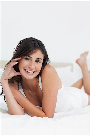 Portrait of a happy woman on her bed Stock Photo - Premium Royalty-Free, Code: 6109-06194941