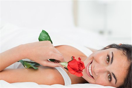 smelling - Portrait of a beauty lying on her back while holding a rose Stock Photo - Premium Royalty-Free, Code: 6109-06194992