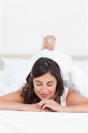 Brunette lying on the belly in her bed Stock Photo - Premium Royalty-Free, Code: 6109-06194922