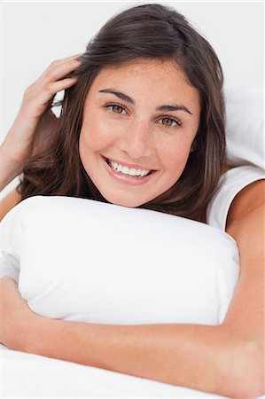 Portrait of a beaming brunette in her bed Stock Photo - Premium Royalty-Free, Code: 6109-06194927