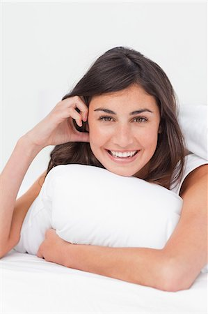 Portrait of a cute brunette in her bed Stock Photo - Premium Royalty-Free, Code: 6109-06194928