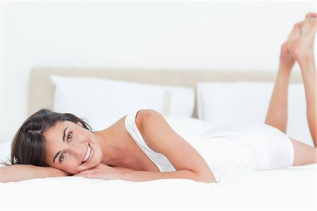 Portrait of a beautiful smiling brunette in her bed Stock Photo - Premium Royalty-Free, Code: 6109-06194933