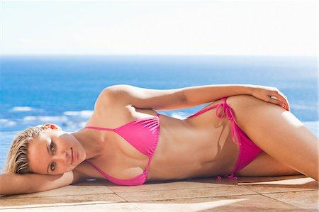 Woman enjoying the sun while lying on the swimming pool edge Stock Photo - Premium Royalty-Free, Code: 6109-06195118