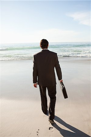 rear - Rear view of a serious businessman walking on the beach Stock Photo - Premium Royalty-Free, Code: 6109-06195331