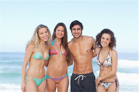 sexy black women in bikinis - Four friends holding each other as they stand by the sea Stock Photo - Premium Royalty-Free, Code: 6109-06195474