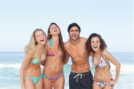 sexy black women in bikinis - Four friends laughing as they hold each other by the sea Stock Photo - Premium Royalty-Free, Code: 6109-06195475