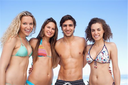 sexy black women in bikinis - Four friends holding each other as they look ahead Stock Photo - Premium Royalty-Free, Code: 6109-06195476