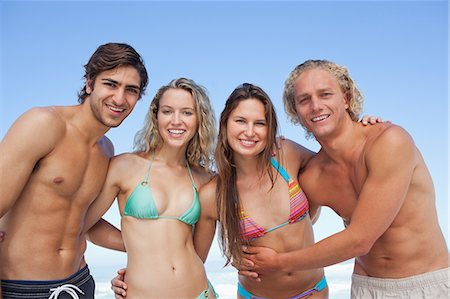 Four friends embracing each other while wearing swimsuits Stock Photo - Premium Royalty-Free, Code: 6109-06195485