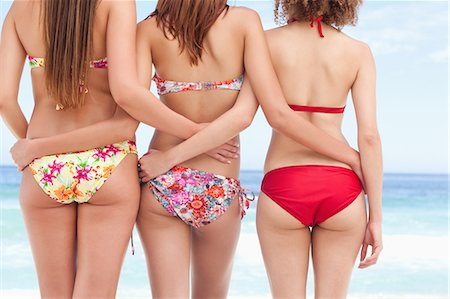 sexy black women in bikinis - Three friends looking at the sea while putting an arm around each other Stock Photo - Premium Royalty-Free, Code: 6109-06195562
