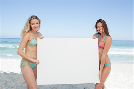 Two friends holding a blank poster by the sea Stock Photo - Premium Royalty-Free, Code: 6109-06195517