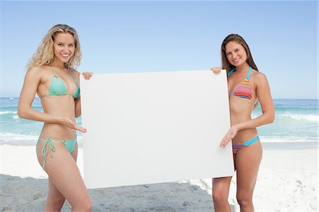 Two friends smiling while holding a blank poster by the sea Stock Photo - Premium Royalty-Free, Code: 6109-06195518