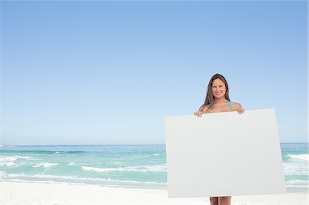 poster - Woman wearing a bikini holding a blank poster in front of her Stock Photo - Premium Royalty-Free, Code: 6109-06195525