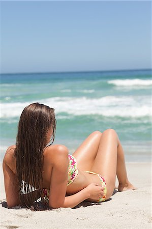 pretty - Woman looking towards the sea as she sunbathes on the sand Stock Photo - Premium Royalty-Free, Code: 6109-06195604