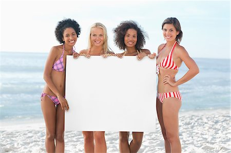 Four women smiling as they hold a large white poster Stock Photo - Premium Royalty-Free, Code: 6109-06195637