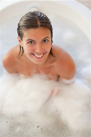Smiling woman sitting in the tub and looking up Stock Photo - Premium Royalty-Free, Code: 6109-06195748