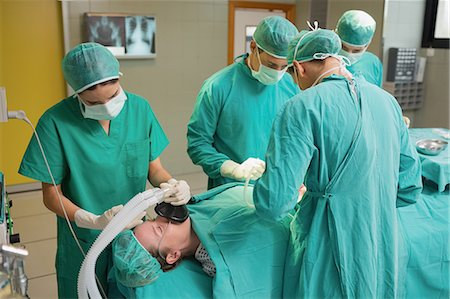 Patient lying on the operating table next to surgeons Stock Photo - Premium Royalty-Free, Code: 6109-06195839