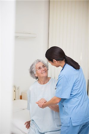 Nurse helping a smiling senior patient Stock Photo - Premium Royalty-Free, Code: 6109-06196000