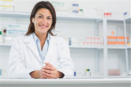 Smiling woman pharmacist behind a counter joining her hands Stock Photo - Premium Royalty-Free, Code: 6109-06196158