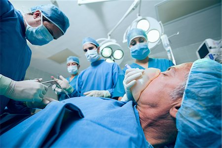 Surgery team in an operating theater operating a patient Stock Photo - Premium Royalty-Free, Code: 6109-06196383