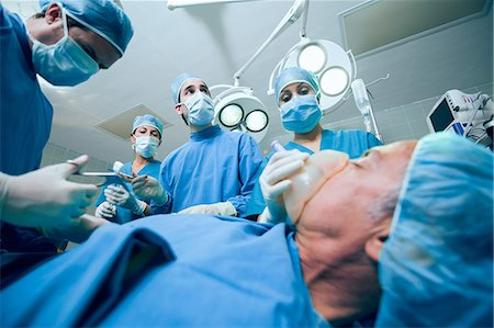 Surgery team in an operating theater operating an unconscious patient Stock Photo - Premium Royalty-Free, Code: 6109-06196384