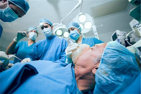 Surgerical team in an operating theater operating an unconscious patient Stock Photo - Premium Royalty-Free, Code: 6109-06196386