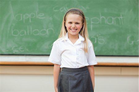 school girl uniforms - Girl standing in front of blackboard Stock Photo - Premium Royalty-Free, Code: 6109-06196567