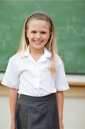 school girl uniforms - Smiling schoolgirl standing in front of blackboard Stock Photo - Premium Royalty-Free, Code: 6109-06196568